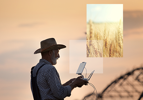 Old farmer with hat holding remote control for drone flying above field with irrigation system in summer